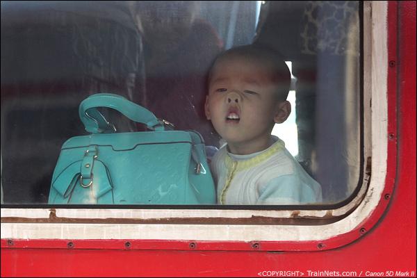 2014年1月20日,深圳西站,前往合肥的列车,一个孩子调皮得对着玻璃做鬼脸。(IMG-2203-140121)