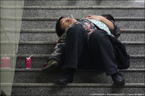 2014年1月25日下午,广州火车站广场。一位父亲抱着孩子在楼梯上熟睡。(IMG-4056-140126)