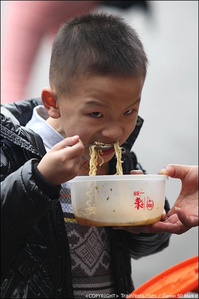 2014年1月25日下午,广州火车站广场。一位孩子狼吞虎咽地吃着午饭。(IMG-4086-140126)