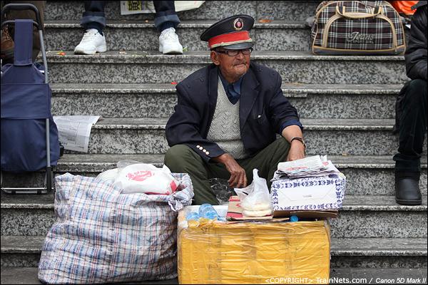 2014年1月25日下午,广州火车站广场。一位穿着铁路制服的摆摊老人。(IMG-4106-140126)