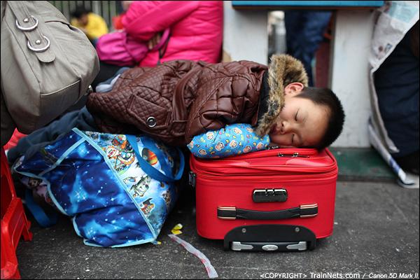 2014年1月25日下午,广州火车站广场。一位前往桂林的小朋友趴在行李上午睡。(IMG-4115-140126)
