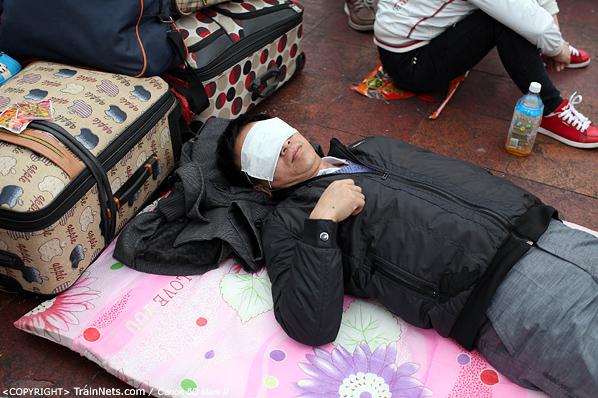 2014年1月25日下午,广州火车站广场。一位乘客用口罩代替眼罩在地上睡觉休息。(IMG-4135-140126)