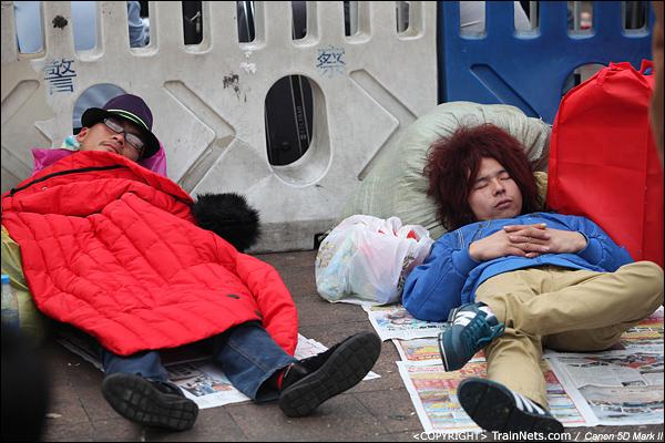 2014年1月25日下午,广州火车站广场。两位打扮新潮的年轻人在地上睡觉休息。(IMG-4245-140126)
