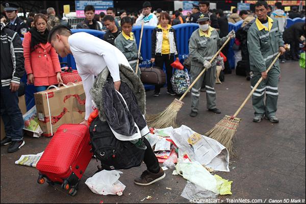 2014年1月25日下午,广州火车站广场。清洁工清扫临时候车区,一名乘客来匆匆起身收拾行李躲避。(IMG-4276-140126)