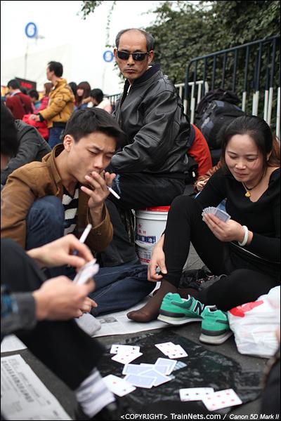 2014年1月25日下午,广州火车站广场。一位戴着墨镜的乘客专心地看着其他人在打牌。(IMG-4292-140126)