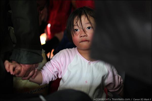 2014年1月25日下午,广州火车站。前往襄阳的列车,一位挤在硬座的小女孩看着窗外。(IMG-4416-140126)