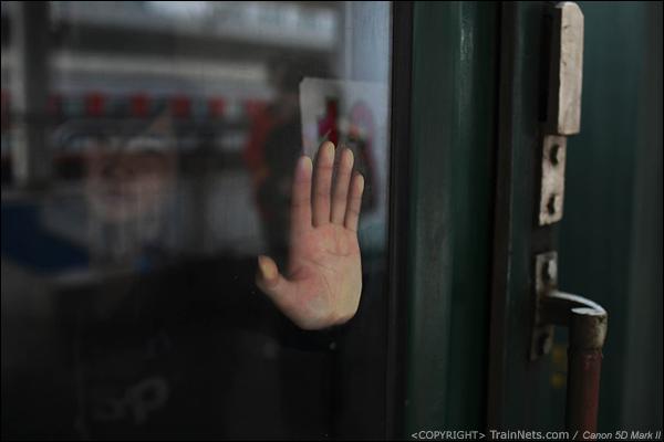 2014年1月25日下午,广州火车站。前往成都的临客,一位无座的乘客站在车门端,扶着车窗玻璃。(IMG-4581-140126)