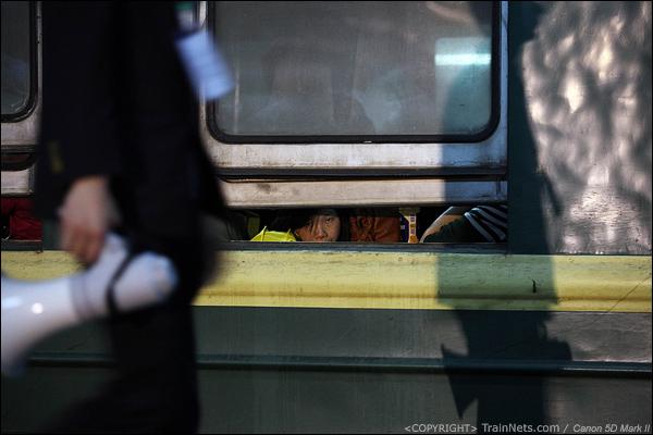 2014年1月25日晚上,深圳西站开往达州的L736次,一位乘客透过窗缝看着外面,站台工作人员的影子映射在绿皮车上。(IMG-4999-140125)