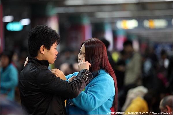 2014年1月26日晚上,深圳火车站,一对情侣在人群中打情骂俏。(IMG-5393-140126)