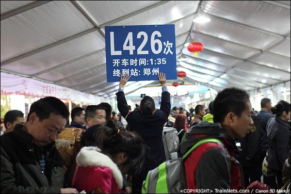 2014年1月26日晚上,深圳火车站,一位工作人员举着L426次站牌,引导乘客进站。(IMG-5425-140126)