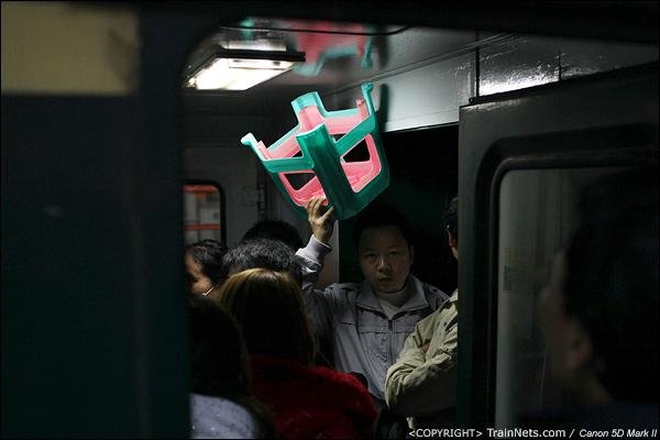 2014年1月26日晚上,深圳开往襄阳的L46次,一位无座乘客被挤得只能举起小板凳。(IMG-5530-140126)
