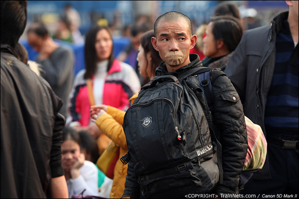 2014年1月27日下午,广州火车站,一名乘客不知为何封着自己的嘴巴,在露天候车区等待进站。 (IMG-5636-140127)