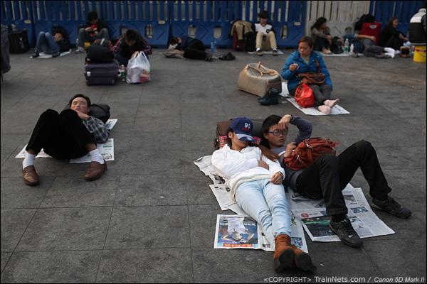 2014年1月27日。下午,广州火车站,乘客躺在露天候车区的地面上,就像躺在沙滩上享受着阳光一样。(IMG-5667-140127)