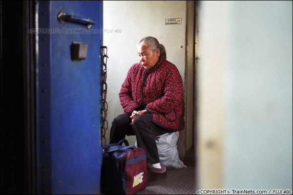 2013年12月21日。7322次离开钦州站后,车厢里再次满员,一位老人坐在车厢连接处。(E3224)