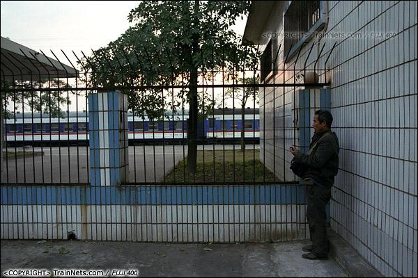 2013年12月21日早晨七点,防城港火车站,候车室还没开放,一位乘客站在出站口旁打电话,站台上停着7322次。(E3304)