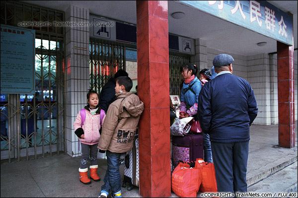 2013年12月21日早晨七点,防城港火车站,候车室还没开放,乘客们聚集在进站口等待。(E3305)