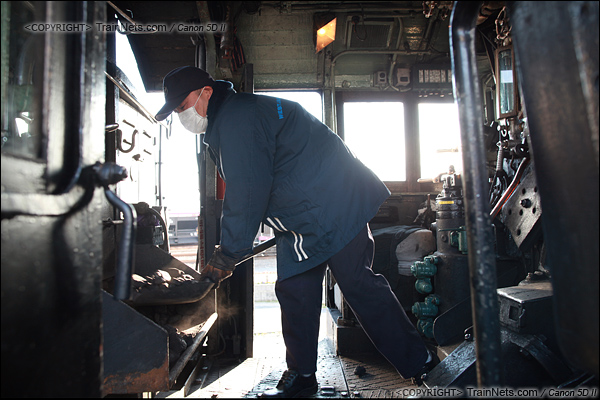 2012年2月2日。日本京都梅小路蒸汽机车博物馆。执行体验之旅的蒸汽机车,司炉正在给锅炉加煤。(IMG-6745-120202)