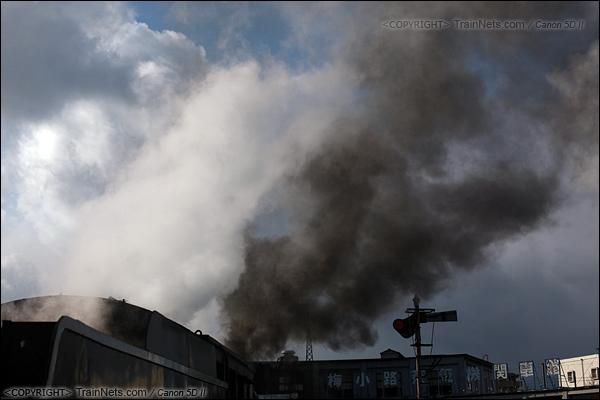 2012年2月2日。日本京都梅小路蒸汽机车博物馆。执行体验之旅的蒸汽机车,司炉正在给锅炉加煤,此时烟囱冒出黑烟。(IMG-6758-120202)