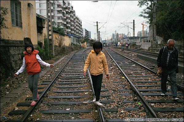 2013年12月。厦门。 金榜路道口往厦门折返段方向,两名刚放学的孩子在比赛走铁路。(E2812)