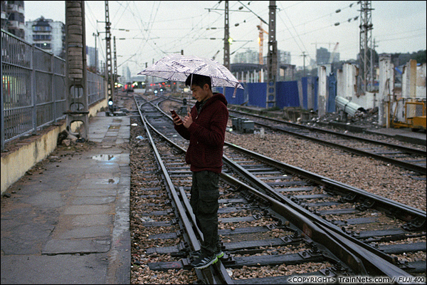 2013年12月。厦门。 金榜路道口,一位年轻人站在铁轨上发短信,远处是厦门站站台。(E2822)