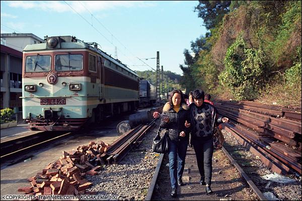 2013年12月。厦门。 早上,准备上班的市民从厦门折返段的机车旁走过。(E2904)