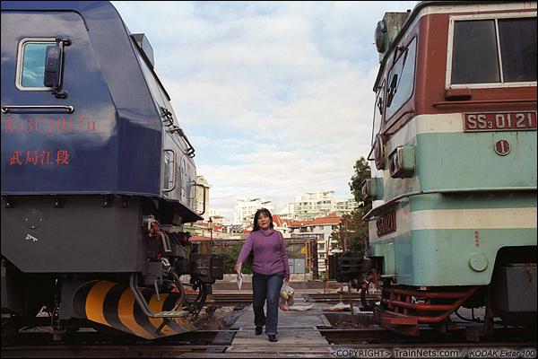 2013年12月。厦门。 早上,准备上班的市民从厦门折返段的机车旁走过。(E2931)