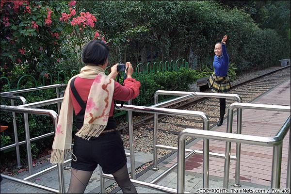 2013年12月。厦门铁路公园。万寿路路口。 路口长着一棵三角梅,一名游客在此处留影。(E3020)