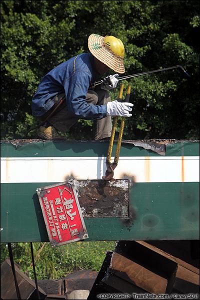 2014年8月31日。韶关机务段。 一名工人用工具把SS1-0710的铭牌敲下。铭牌就是机车的身份证,标有型号、生产厂家、生产日期。(IMG-9388-140831)