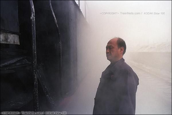 2014年2月。甘肃省白银矿区铁路,351次通勤车。白银市区的临时站,蒸汽机车司机正在对机车进行检查,忽然一股蒸汽喷涌而出,司机被熏得睁不开眼。(E3518)