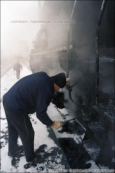 2014年2月。甘肃省白银市的白银矿区铁路,仍采用蒸汽机车作为动力。在市区的临时车站,蒸汽机车司机对机车进行检查。(E3521)