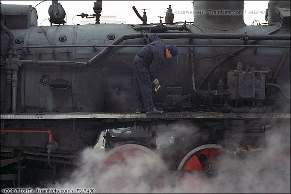 2014年2月。甘肃省白银矿区铁路,353次通勤车。发车前,司机爬到蒸汽机车上往风泵压油机里添补润滑油。(E3618)