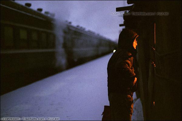 2014年2月。甘肃省白银矿区铁路,353次通勤车。白银市区的临时站,清晨天仍是蒙蒙亮,一位职工在站台上的小卖部前购买香烟。(E3629)