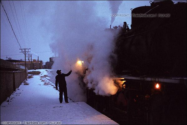 2014年2月。甘肃省白银矿区铁路,353次通勤车。白银市区的临时站,司机正在对位于列车后部的机车进行检查。由于连日大雪导致线路湿滑,因此需要两台上游蒸汽机车推挽式牵引绿皮车上山。(E3633)