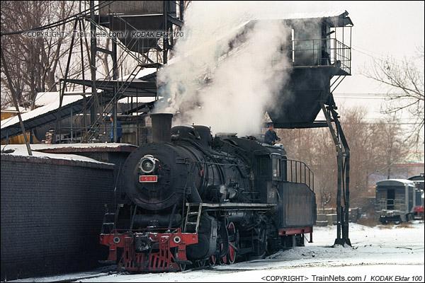 2014年2月。甘肃省白银市的白银矿区铁路,仍采用蒸汽机车作为动力。在牵引完早晨第一趟进入山内矿区的通勤绿皮车后,机车回到机务段,司机正在为机车加水加煤。(E3823)