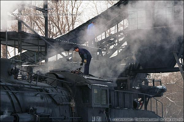 2014年2月。甘肃省白银市的白银矿区铁路,仍采用蒸汽机车作为动力。在牵引完早晨第一趟进入山内矿区的通勤绿皮车后,机车回到机务段,司机正在为机车加水加煤。(E3824)