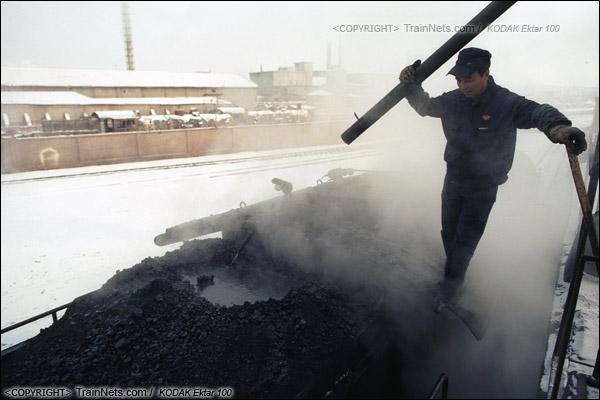 2014年2月。甘肃省白银市的白银矿区铁路,仍采用蒸汽机车作为动力。在牵引完早晨第一趟进入山内矿区的通勤绿皮车后,机车回到车库里,司机正在为机车加煤。(E3836)