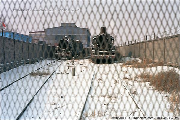 2014年2月。甘肃省白银矿区铁路公司站。车库的高墙里停放着已经报废了的蒸汽机车。(E3901)
