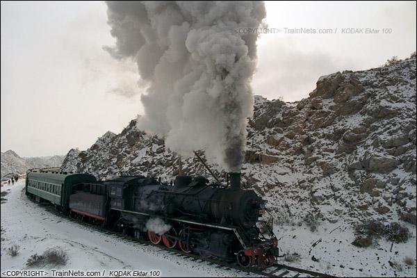 2014年2月。甘肃省白银矿区铁路,353次通勤车。早晨8点,第一班进入矿区的通勤车停靠在东长沟站后再次从大坡道上启动,蒸汽机车喷出浓浓黑烟。(E3915)