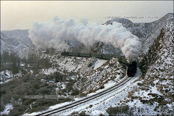 2014年2月。甘肃省白银矿区铁路,353次通勤车。农历新年后第一天上班,乘坐通勤车进山的职工很多,同时由于大雪导致线路湿滑,因此两台上游蒸汽机车推挽式牵引着满载上班职工的绿皮通勤车进山。这里是中国最后的一个有蒸汽机车牵引绿皮车的地方。(E4013)