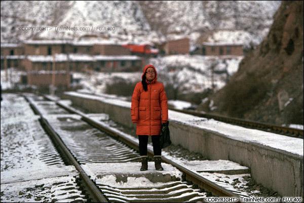 2014年2月。甘肃省白银矿区铁路三冶炼站。早晨,一位刚下班的职工站在铁路上等待下山的通勤车。(E4019)