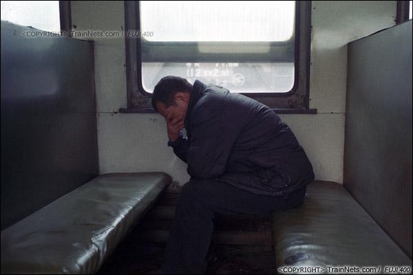 2014年2月。甘肃省白银矿区铁路,355次通勤车。一位乘坐通勤车上班的职工在车上打盹。(E4316)