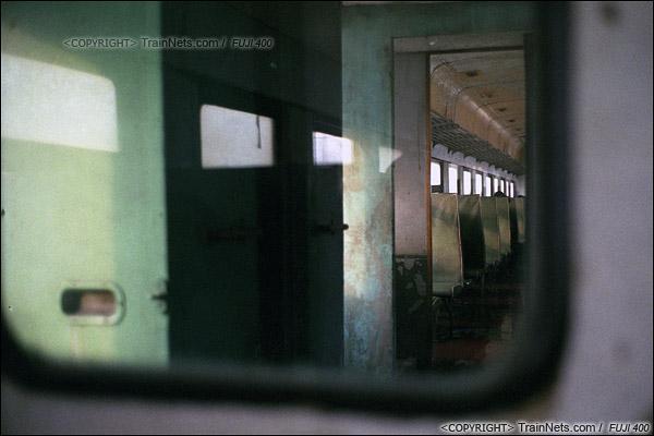 2014年2月。甘肃省白银矿区铁路,355次通勤车。夕阳照射在进入矿区的绿皮车里,这种隶属于企业的绿皮车厢,保养都十分随意,许多地方都很残旧。(E4322)
