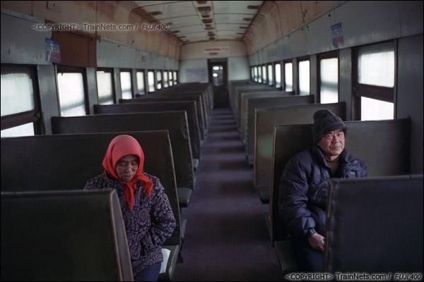2014年2月。甘肃省白银矿区铁路,351次通勤车。傍晚六点,夜里最后一班进入矿区的通勤车上,两位乘客坐在车上等待发车。(E4333)