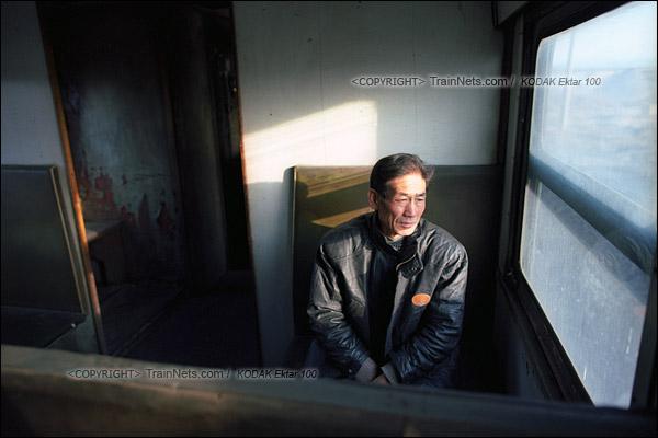 2015年1月。甘肃省白银矿区铁路。356次通勤车。一位乘客看着窗外的风景。(F0223)