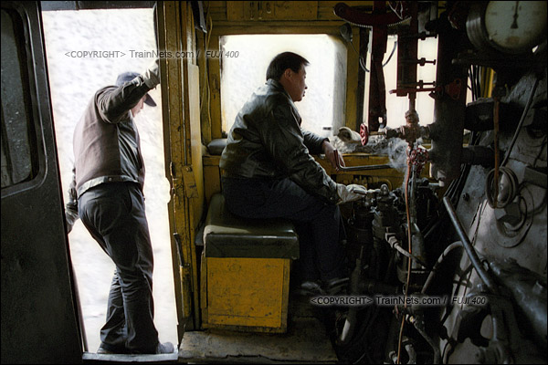 2015年1月。甘肃省白银铁路。下午,355次通勤车从三冶炼站开出,准备开始艰难地爬坡。两名司机专心地看着前方的线路。(F0513)