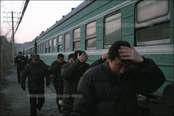 2015年1月。甘肃省白银矿区铁路。353次通勤车抵达深部铜矿站。由于出站时需要经过蒸汽机车,职工纷纷用手挡着头顶,防止煤灰掉进头发。(F0613)