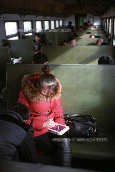 2015年1月。甘肃省白银铁路。下午,355次通勤车,一位乘客坐在车里看电视剧打发时间。(F0618)