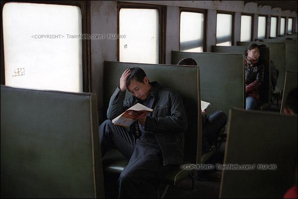 2015年1月。甘肃省白银铁路。下午,接载职工下班的356次通勤车,几位乘客看书消磨时间。(F0619)