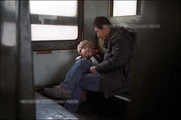 2015年1月。甘肃省白银铁路。下午,接载职工下班的356次通勤车,父亲与孩子在车上聊天。(F0621)