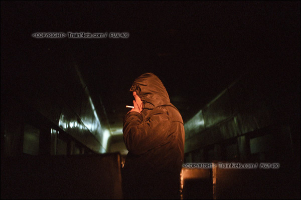 2015年1月。甘肃省白银铁路。天未亮,353次通勤车等待发车。蒸汽机车的车灯灯光照射进漆黑的车厢里,不少乘客借着灯光找寻座位。(F0634)